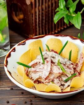 Ensalada de carne con rodajas de tomate juliana y mayonesa servida con papas fritas