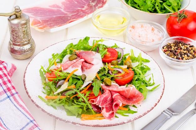Ensalada casera fresca con rúcula, jamón, rúcula, tomate, parmesano.