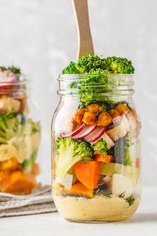 Ensalada casera saludable de mason jar con verduras al horno, hummus, tofu y garbanzos.