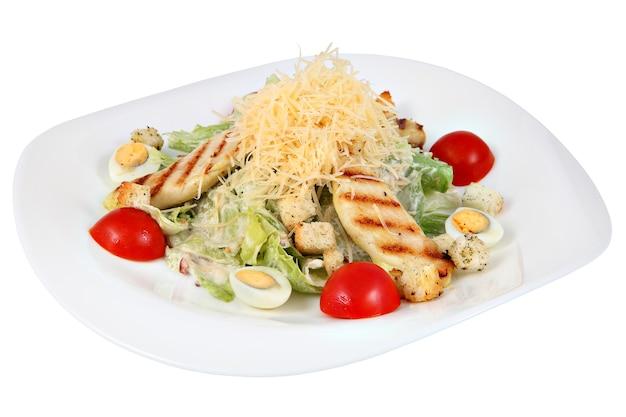 Ensalada césar clásica con pollo y lechuga, plato ovalado, aislado sobre fondo blanco.