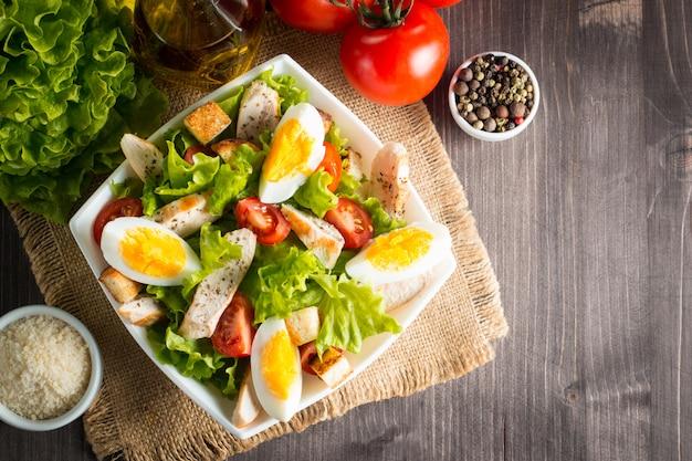 Ensalada césar fresca con deliciosa pechuga de pollo, ruccola, espinacas, repollo, rúcula, huevo, parmesano y tomate cherry sobre fondo de madera. aceite, sal y pimienta. concepto de comida sana y dieta.