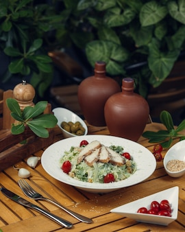 Ensalada césar griega con carne blanca, lechuga y tomates cherry dentro de un plato blanco sobre una mesa de madera.