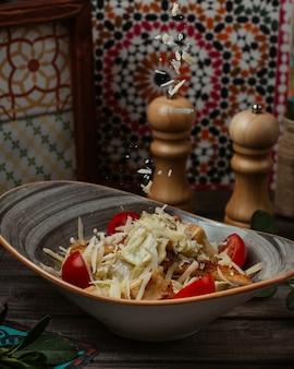 Ensalada césar con parmesano picado y tomates cherry freah en un recipiente rústico.