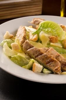 Ensalada césar con picatostes y pollo a la plancha sobre mesa de madera