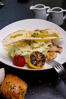 Ensalada césar pollo lechuga tomate parmesano anchoas vista lateral