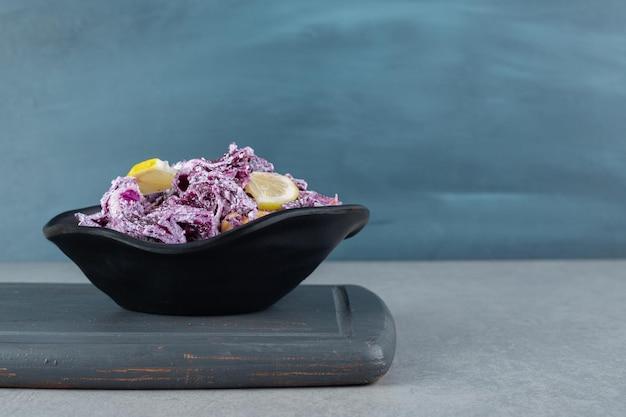 Ensalada de col y cebolla morada picada en un plato sobre la mesa de hormigón.
