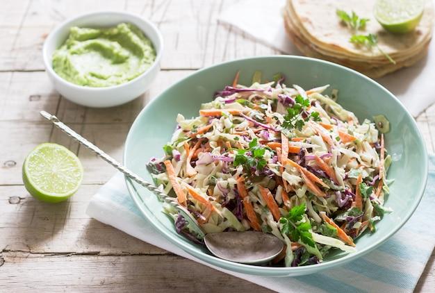 Ensalada de col hecha de repollo, zanahorias y varias hierbas, servida con tortillas y guacamala