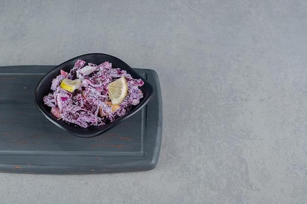 Ensalada de col morada y cebolla en una taza de cerámica.