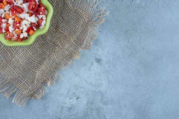 Ensalada de coliflor y pimiento en un recipiente verde sobre mesa de mármol.