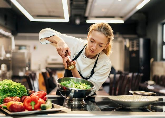 Ensalada de condimentos chef femenina en la cocina
