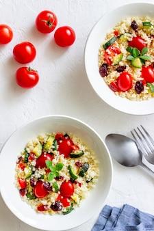 Ensalada de cuscús con tomates, pimientos, calabacines y arándanos. comida vegetariana. dieta. alimentación saludable.