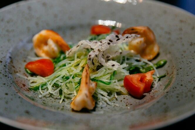 Ensalada de camarones, tomates y fideos de arroz, calabacín en plato blanco.