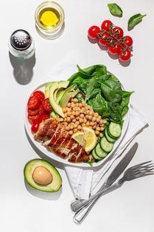 Ensalada dietética con pollo aguacate pepino tomate y espinacas hard light