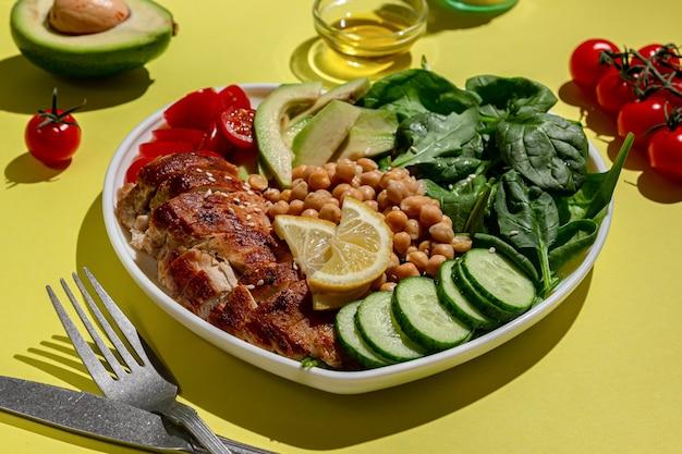 Ensalada dietética con pollo aguacate pepino tomate y espinacas