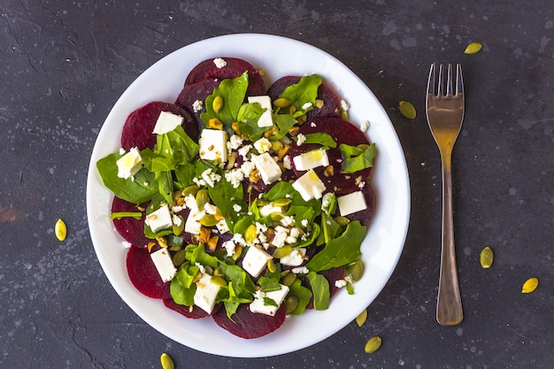 Ensalada dietética de remolacha, rúcula, queso feta, semillas de calabaza con aceite de oliva.