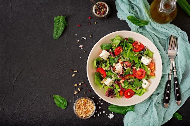 Ensalada dietética con tomates, queso feta, lechuga, espinacas y piñones.