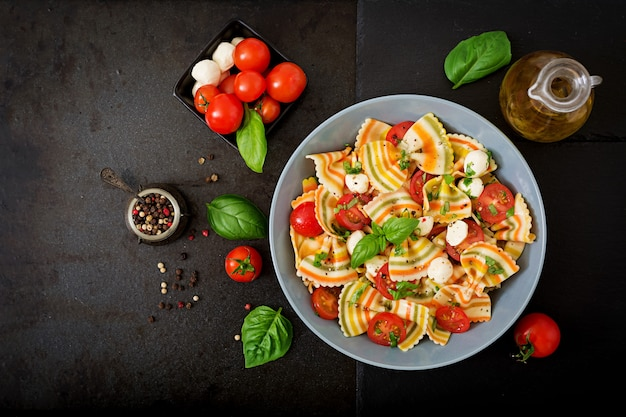 Ensalada farfalle color pasta con tomate, mozzarella y albahaca.