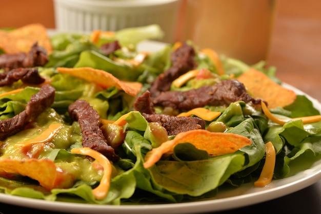 Ensalada, filet mignon y chips de tortilla