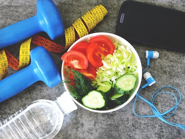 Ensalada de fitness, pesas y cinta métrica