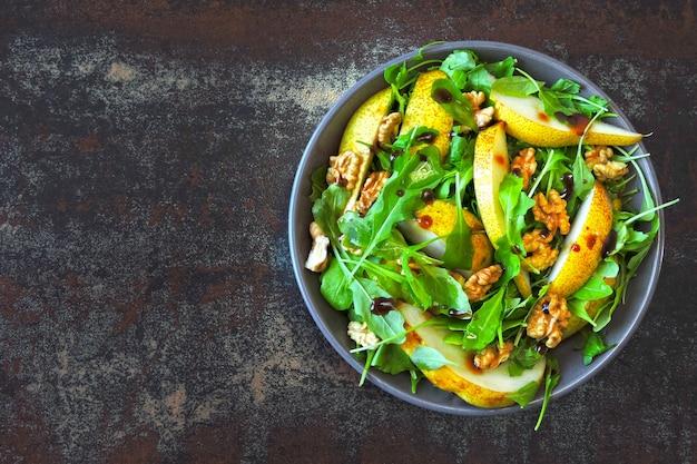 Ensalada de fitness rúcula pera nuez. alimentos coloridos y saludables en estilo flatlay.