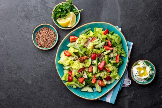 Ensalada de fresa lechuga saludable con semillas de lino en placa azul vista superior