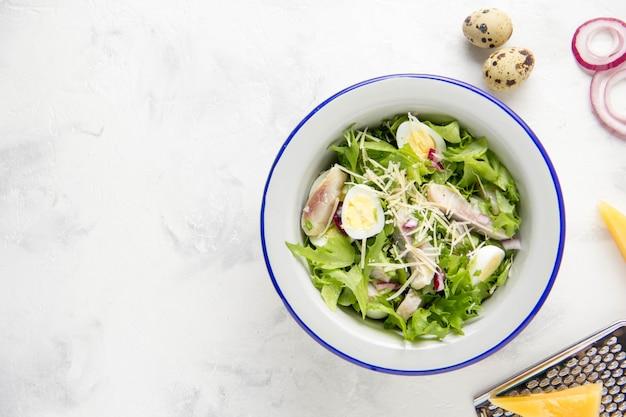 Ensalada fresca con arenque salado, pescado, lechuga, huevos de codorniz hervidos, cebolla roja y queso parmesano duro
