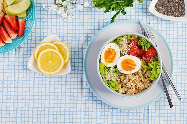 Ensalada fresca con avena, tomate, lechuga, microgreens y huevo cocido y plato de frutas