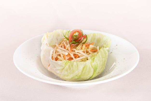 Ensalada fresca de col servida en una ensaladera, decorada con hierbas, colocada en un plato blanco