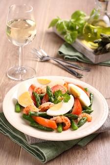 Ensalada fresca con espárragos, huevos, camarones y tomates.