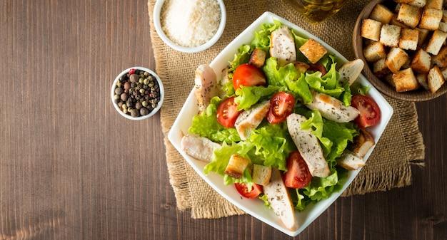 Ensalada fresca hecha de tomate, rúcula, pechuga de pollo, huevos, rúcula, galletas y especias. ensalada césar en un recipiente blanco y transparente sobre fondo de madera