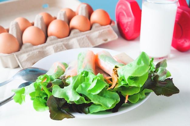 Ensalada fresca con huevo y leche, menú saludable con pesas rojas, concepto de estilo de vida saludable