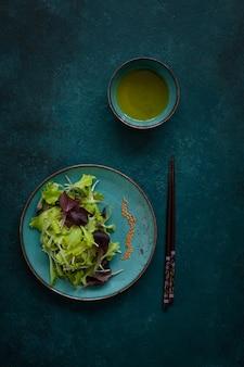 La ensalada fresca mezclada del bebé se va con aceite de oliva y palillos en fondo verde