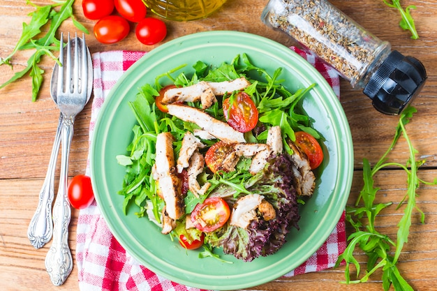 Ensalada fresca con pechuga de pollo, rúcula y tomate. vista superior