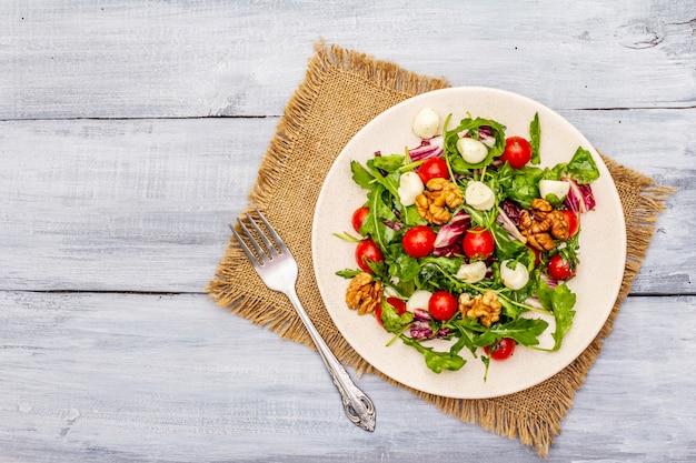 Ensalada fresca con rúcula, achicoria, tomate cherry, mozzarella baby, nueces