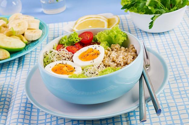 Ensalada fresca. tazón de desayuno con avena, tomates, lechuga, microgreens y huevo cocido