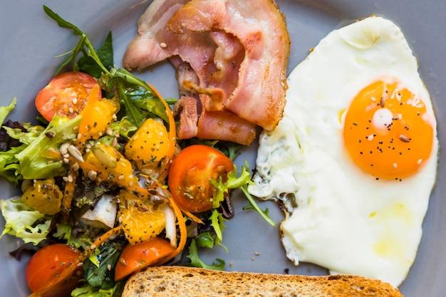 Ensalada fresca; tocino; mitad de huevos fritos y pan tostado en plato gris.