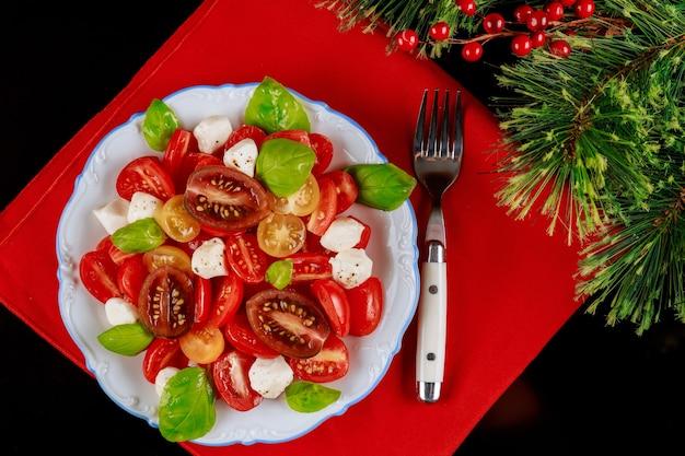 Ensalada fresca con tomates cherry, pepinos y queso mozzarella. mesa de la cena de navidad.