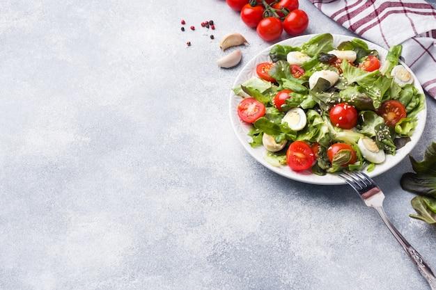 Ensalada fresca con tomates y huevos de codorniz y lechuga. copia espacio
