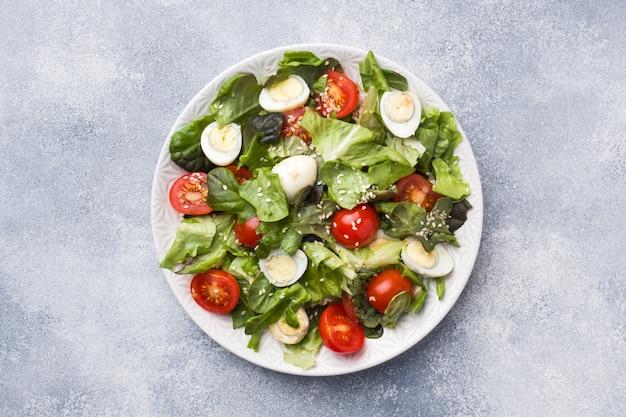 Ensalada fresca con tomates y huevos de codorniz y lechuga.