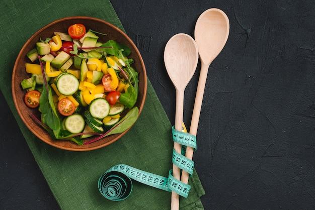 Ensalada fresca de vegetales mezclados con cuchara de madera y cinta métrica en servilleta verde sobre fondo de concreto
