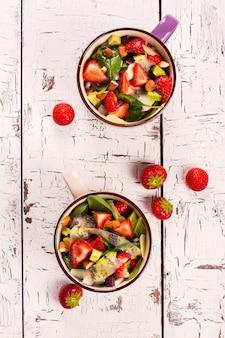 Ensalada fresca del verano con la fresa, el aguacate y la espinaca en el fondo de madera rústico blanco