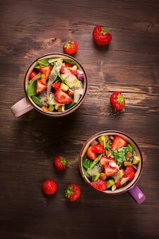 Ensalada fresca del verano con la fresa, el aguacate y la espinaca en fondo de madera rústico. vista superior