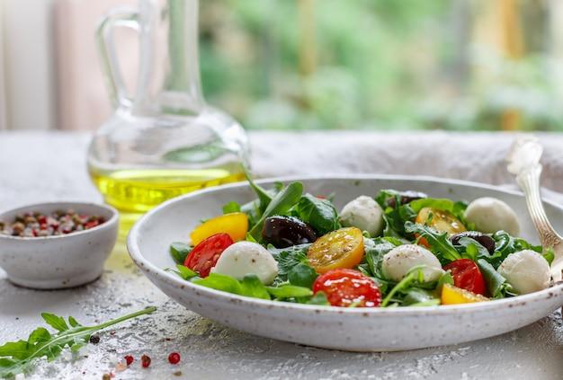 Ensalada fresca de verano con rúcula, tomates cherry amarillos y rojos, aceitunas kalamata y mozzarella