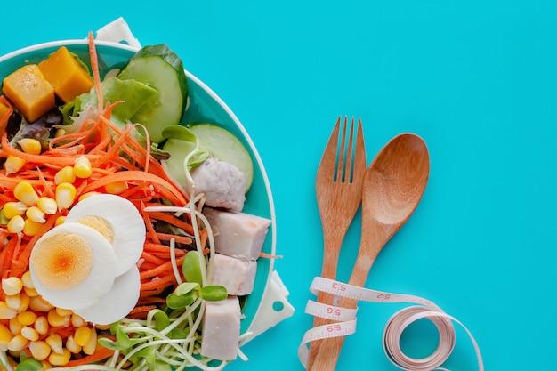 Ensalada fresca de verduras con huevo de gallina hervida, cinta métrica, cuchara de madera y tenedor sobre fondo azul