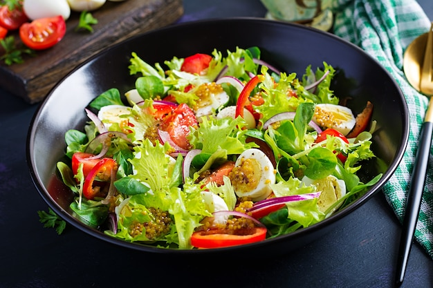 Ensalada fresca con verduras tomates, cebollas rojas, lechuga y huevos de codorniz. concepto de dieta y alimentos saludables. comida vegetariana.
