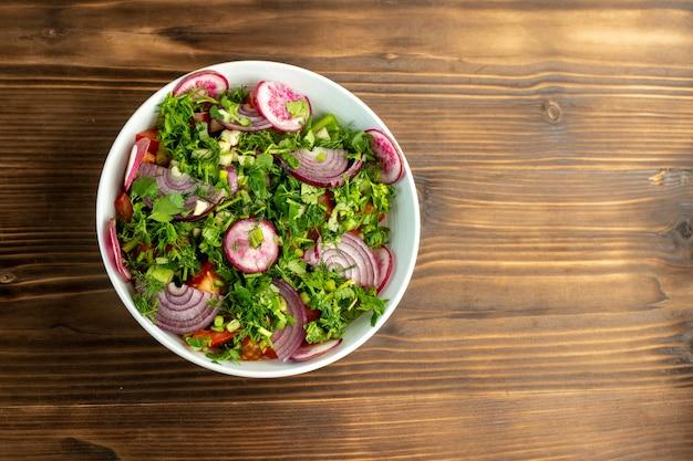 Ensalada fresca vitaminada rica en colorido con rábano cebolla roja y tomates en el interior con verduras en la parte superior en la superficie rústica de madera