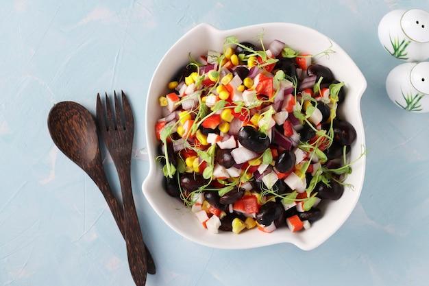 Ensalada con frijoles negros, maíz, palitos de cangrejo y microgrines de guisantes en un recipiente blanco sobre una mesa azul claro, vista desde arriba