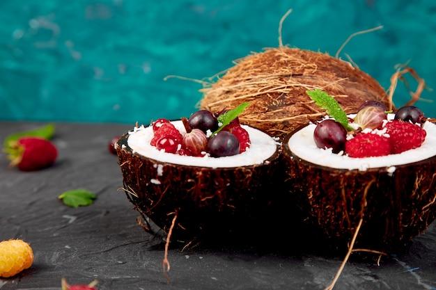 Ensalada de frutas agrus, grosella, frambuesa en un tazón de cáscara de coco