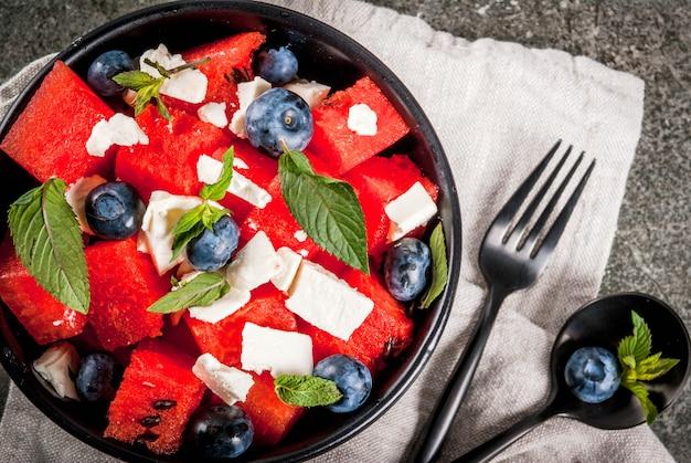 Ensalada de frutas y bayas de verano: sandía, arándanos, menta, queso feta y salsa balsámica. sobre un cuenco negro, mesa de piedra negra. con ingredientes, tenedor, cuchillo. vista superior de copyspace