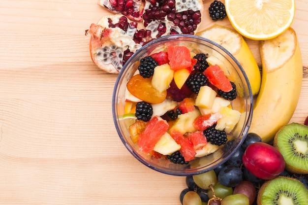Ensalada de frutas coloridas en un tazón de vidrio en el escritorio de madera